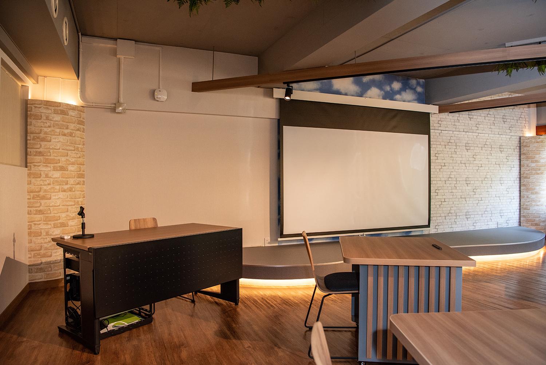 スクリーン、プロジェクター、マイクなどが付いていて、貸切時はシアター形式で最大59席まで設置可能