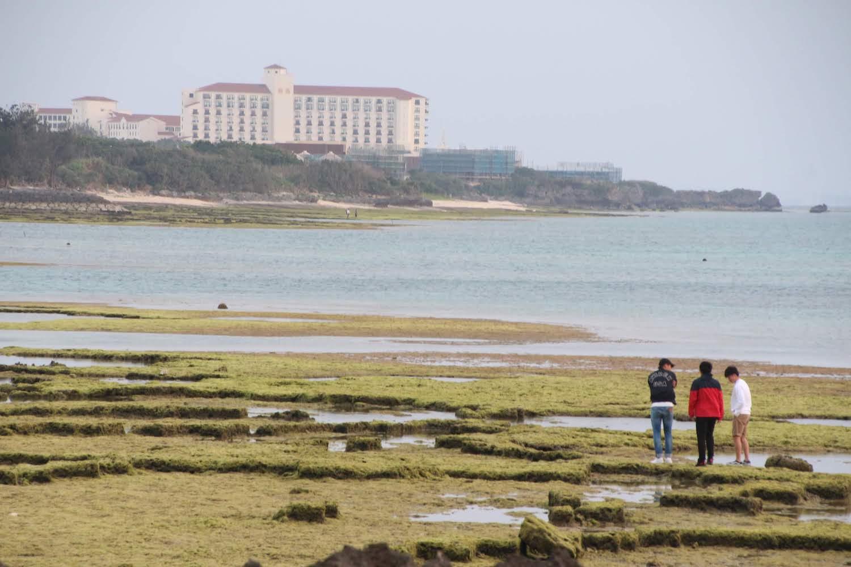残波岬の対岸の方に見える白い建物はホテル日航アリビラ